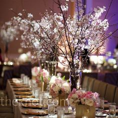 Center piece - Arrangements of tall cherry blossom branches and extra candles made the head table stand out from the rest at the reception.