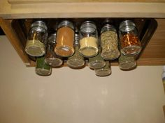 Super-Easy-and-Cheap-Magnetic-Spice-Rack. A magnetic spice rack. A cookie sheet screwed to the under side of the cupbaord. Then magents hot glued to the lid of baby food jars.