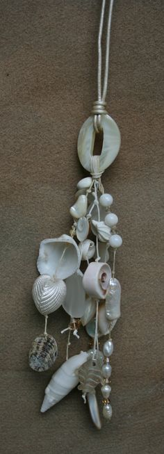 SALE!!!--White mother of pearl oval pendant suspends a tassel of natural shells, pearls, shell beads, seaglass, and Swarovski crystals