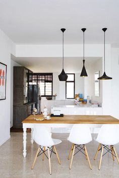 Black lamps - The all-white walls complement the white-and-wood dining set.