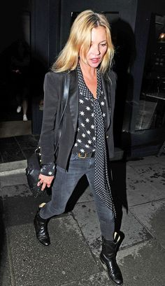 Kate Moss wears a star print blouse with a skinny scarf, blazer, belted skinny jeans, cowboy boots, and a black saddle bag