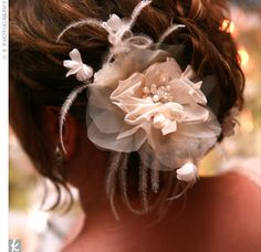 The bride swept her curls into a loose bun and accented it with a white silk flower and feather hairpin.