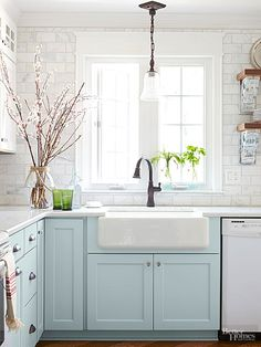 An enlarged window above the sink allows plenty of sunlight to stream into the cottage kitchen. An apron-front sink and oil-rubbed bronze faucet contribute vintage appeal. A marble-tile backsplash, installed by the homeowner, shimmers against pale blue base cabinetry.
