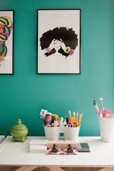 A chic workspace with teal walls and graphic art