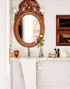 An ornate, gilded mirror and small art elevate the look of this powder room, while a white shelf adjacent to the floating sink provides a surface for grooming essentials.