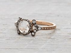 Made in 18k rose gold and centered with a .99 carat rose cut diamond set in oxidized silver. Accented with .10 carats of single cut diamonds. Romantic like its namesake flower, this ring is sweet but slightly mysterious. She isn't the sparkliest, but what she lacks in brilliance she makes up for in soft scrollwork and delicate texturing. We strive to use antique rose cut diamonds whenever possible. Our jewelry is always forged with recycled metals and made in New York City by the hands of…