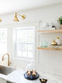 Lighting over sink White and gold kitchen features white shaker cabinets adorned with brass pulls paired with calcutta marble countertops and a white subway tile backsplash. Classic Kitchen, New Kitchen, Kitchen Dining, Kitchen Decor, Kitchen White, Kitchen Wood, Kitchen Ideas, Kitchen Shelves, Kitchen Cabinets