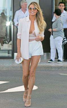 Body Envy from Chrissy Teigen's Street Style  The model is rocking a knit body suit under white shorts and a cream jacket.