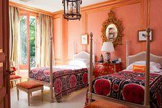 A papaya, coral, orange bedroom interior with suzeni covers.