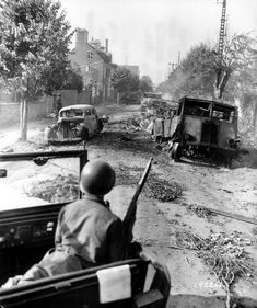 GIs passing by burned out automobiles in Avranches, which was liberated by the 4th Infantry Division and the 2nd French Armored Division, 1944