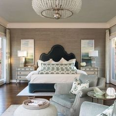 Elegant and stylish... Textures, patterns and many different warm shades of color blend together seamlessly! Design by @traciconnellinteriors #bedroom #bed #headboard #wallpaper #neutrals #bedding #nightstand #endtable #lamps #chairs #rug #frenchdoors #drapes #chandelier #lighting #pillows #art #interiordesign #interior #pouf #design #decorate #home #masterbedroom #decor #homedecor #homedesign #footrest #elegant #style