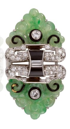 AN ELEGANT ART DECO PLATINUM, ONYX, DIAMOND AND JADE DOUBLE CLIP BROOCH, 1930S. Each terminal set with triangular carved jade motifs highlighted by single-cut diamonds, black enamel and onyx.