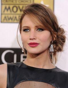 Le gros chignon que porte Jennifer Lawrence a été positionné bas dans sa nuque et est assez décentré. Le coiffeur a tracé une raie sur un cô...