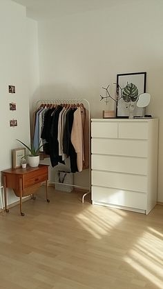 Bedroom organization | coat hanger | tall dresser with decorative organization on top | wood bedside table | small photos on wall