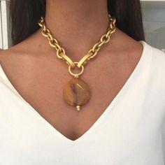 Collar corto compuesto por una tira de perlas de rio blancas y otra tira de cadena de aluminio bañada en oro mate. Ambas tiras están rematadas con una argolla b