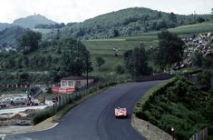"Phil Hill in his Ferrari Testarossa passes the bridge at ""Breidscheid"" during the 1000 km Race 1959. In the background one can see the Nürburg above the whole scenery."