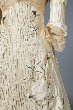 3D floral appliques and rows of sparkling sequins set off this 1900 evening gown.