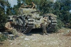 A Churchill Tank, possibly of the 51st Royal Tank Regiment, is given a final check in a harbour area of Italy.