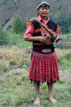 """""""The Idu Mishmi live in the Dibang valley in Arunachal Pradesh. The more you move northwards in the valley, the more shamanism becomes prevalent. The costume of the shaman is fantastic with its decorations, tiger teeth collar and bells on the back. Men traditionally wear a white loin cloth, a jacket with red embellishments and a typical cane hat. Women's traditional dress is black also with reddish embellishments."""""""