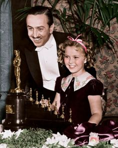 Walt Disney and Shirley Temple with his Oscar (and seven mini Oscars) for Snow White and the Seven Dwarfs.