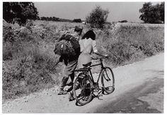 [Italian soldier and woman with bike following captured comrades as they march off to a POW camp, near Nicosia, Sicily]