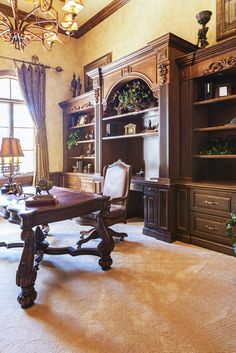 A traditional and ornate home office with large built-ins behind the desk. The beautiful carved desk is the jewel of the room. Do you like the grandiose style of this room?