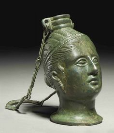 An Etruscan bronze balsamarium, c.3 rd century b.c.  in the form of a female head, perhaps Turan (Aphrodite) or a Lasa, hair bound with fillet in melon-coiffure, with tresses escaping, wearing earrings with inverted pyramidal pendants, with articulated eyes, surmounted by ribbed vessel mouth with two suspension loops, with attached suspension chain