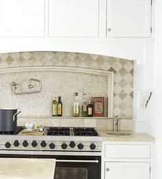 Decorative tile subtly draws attention to a range. The recessed portion -- distinguished by border tile -- mirrors the arc of the entire range area. Over-the-range cabinetry conceals the vent and task lighting while also providing storage.
