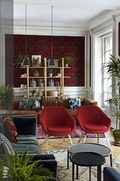 Das Wohnzimmer erhält durch die rot-grau gemusterte Wandtapete einen exotischen Look. Das Holzregal, die Zimmerpflanzen und die hellen Holzdielen verstärken den Stil, während die zwei Polsterstühle in Rot als Blickfang in der Mitte des Zimmers platziert wurden.