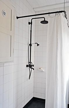 Black shower curtain rod from old metal fittings; the ceiling is lined with wood sourced from the surrounding forest, protected with a coat of white linseed-oil paint. The ceramic tiles are from Finnish company Pukkila.