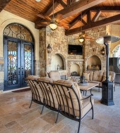 Tuscan outdoor living space with open beams, arched wrought iron double door and fireplace... ᘡղbᘠ