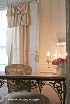 DIY - Salvage Door & Drop Cloth Ruffled Curtains (separate tutorials).  FORGET ABOUT THAT...what I really like is the DESK!  This gives me an idea to take an old table/desk, paint it, and then go to Hobby Lobby and buy some metal corner brackets (they have some gorgeous scroll ones in all different sizes...but wait until they are on sale , which is about every other week) and put in corner of leg/desk top.  It would really class up an old desk/table.