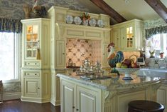 Love the French Country kitchen buttercream colored cabinets, blue toile, roosters, the beamed ceiling, I just love it!