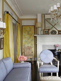 A framed midcentury wallpaper panel brightens a dark living room corner.