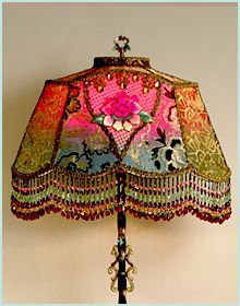 Decorative antique lamp base has been hand-painted and holds a hand-dyed Lotus silk Peony lampshade. The shade is ombre-dyed from fuschia into teal green. The shade is covered on the sides with gold metallic lace and the front is overlaid with beautiful gold and black embroidered net. The center panels feature antique Chinese lotus applique which are framed on the top by very old gold metal passementerie trim. The shade has hand beaded fringe in matching tones. #victorianbeauties
