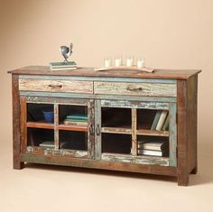 Store treasures and serveware in plain sight in this rustically distinctive sideboard, handcrafted in wood reclaimed from demolished buildings, showing its unique character through weathered paint. Two spacious drawers, one fixed shelf behind mullioned glass doors, cast iron hardware.