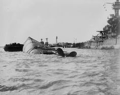 Pearl Harbor 7th Dec 1941, the USS Oklahoma (BB-37) has capsized while the USS Maryland (BB-46) is listing in the background.