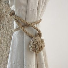 Rope tie backs and white woven curtains to give the impression of sails.