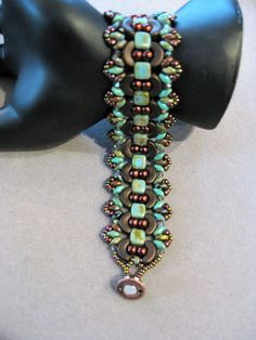 This is a really pretty bracelet pattern with Bronze Arcos, Green Turquoise Tiles, Burgundy Pearls and Iris seed beads. It has a bronze and Diamond magnetic clasp which is so pretty and easy to put on and off. The Its 6 3/4 inches long and 1 inch wide. The pattern is by Michelle