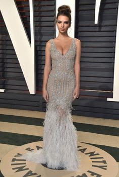 Emily Ratajkowski in a silver beaded gown with feather trimmed skirt