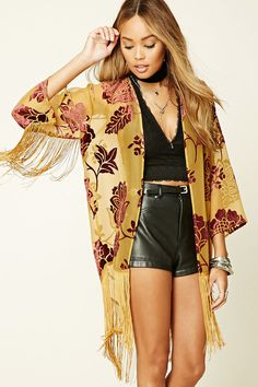 A woven mesh Kimono featuring a velvet floral print, a high-low silhouette, 3/4 fringed sleeves, an open front, a fringed hem, and a V-shape back hem.