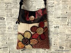This listing is for a crossbody hobo style bag. It is designed using warm earth tones with touches of deep red. The two scrappy flower designs