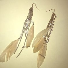 Tan feather dangle earrings Beautiful and stylish tan colored feather earrings. Dangles have gold chains with rhinestone and white bead details. Lightweight.  Does NOT come with backings. Jewelry Earrings