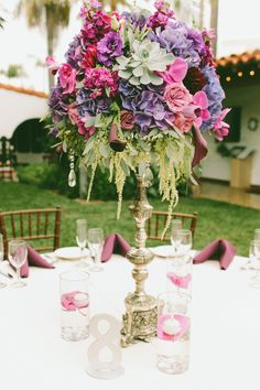 Lovely Tall Wedding Centerpiece with all shades of pinks & purples with a few succulents. Just Gorgeous!! See more here: http://www.StyleMePretty.com/california-weddings/2014/04/14/pink-purple-orange-county-wedding/ Photography: Wai Reyes Photography - waiphoto.com Floral Design: FloralsByJenny.com