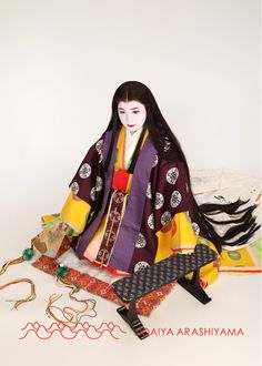 A woman dressed in junihitoe at a kimono photography experience. By her is a beautiful arm rest.