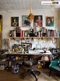 studio - now this is a working artist! A messy desk filled with paint and brushes, a plethora of books, and finished paintings. LOVE IT