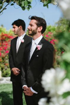 The groom's pink boutonniere really pops against the black tuxedo.