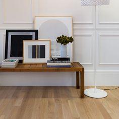 Piso de madeira, móvel de madeira, parede branca e luminária branca.