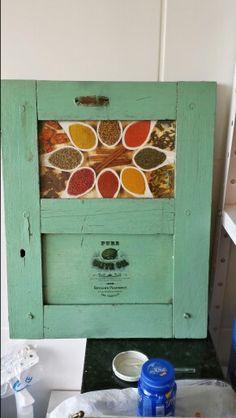 Antiga porta de caixa de entrada de energia elétrica transformada em decoração com motivos culinários.