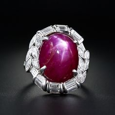 A six-legged star radiates atop this vibrant red, 20 carat cabochon ruby of Burmese origin, accompanied by an AGL certificate stating Burma origin, no Heat. The gemstone is nestled inside a platinum and diamond mounting composed of small marquise diamonds and rolling baguette diamonds totaling 3.00 carats. A distinctive, substantial and important looking ruby ring, circa 1930s.